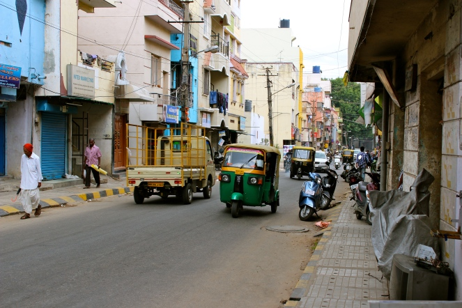 This is a typical street scene in India. The vehicle in the middle is an auto-rickshaw wich is the most common mode of public transportation.