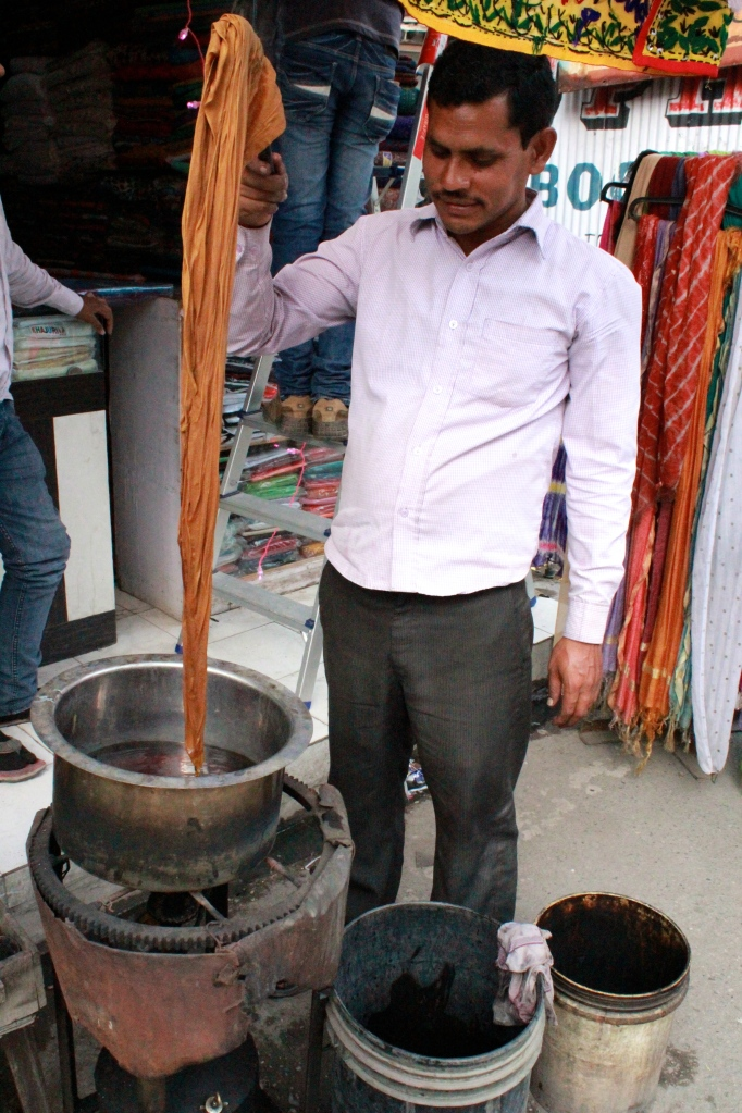 "This man is dying a scarf to match other pieces of an outfit. He would put small amount of powdered dye into the hot water to darken the color. He would then ""blanch"" the scarf to cool it off, dry it over the flame and check to see if the color matched."